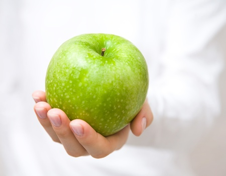 largely: The big green apple in beautiful female hands