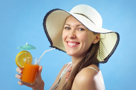 Portrait attractive brunette woman in big hat with orange drink and on the blue background photo