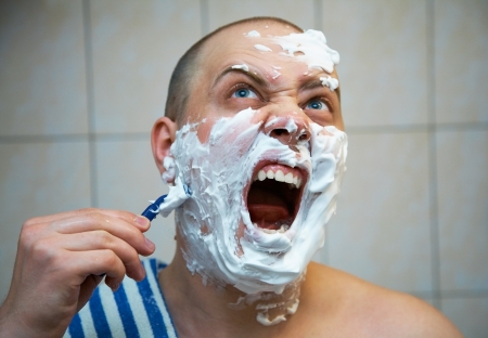 young bald man grimacing breyas in the bathroom