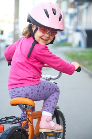 andando en bicicleta: retrato de una chica divertida con una bicicleta Foto de archivo