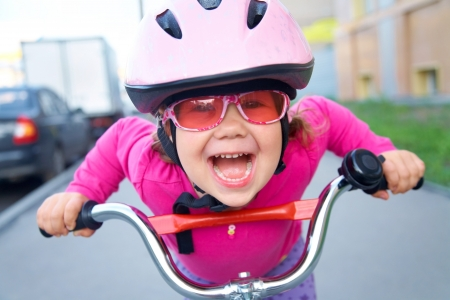 Portrait of a playful funny girl in a pink safety helmet on her bike photo