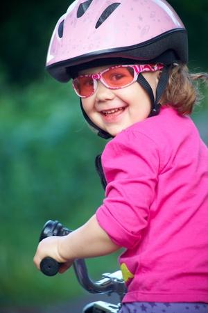 Portret van een klein meisje op een fiets in de zomer park buiten Stockfoto