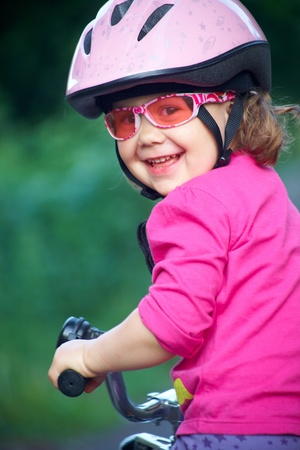 riding helmet: Retrato de una ni�a en una bicicleta en el Parque de verano al aire libre