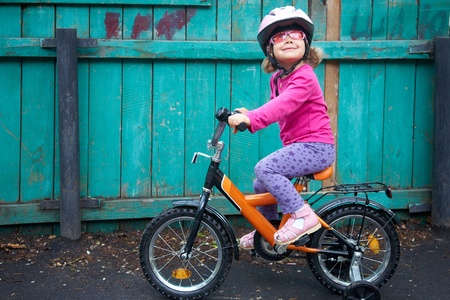A little dreamy girl in pink glasses riding a bicycle in slums  photo