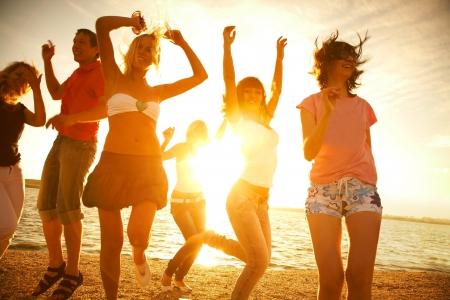 fiesta: Grupo de jóvenes felices bailando en la playa en el atardecer de verano hermosa