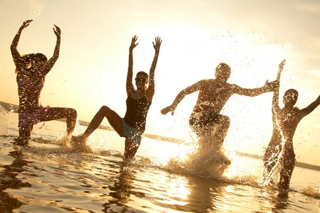 man jump: group of happy young people dancing and spraying at the beach on beautiful summer sunset