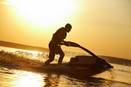 starken Mann springt auf den Jetski über das Wasser bei Sonnenuntergang. Silhouette. sprühen.
