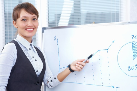young businesswoman drawing graph on chart in office photo
