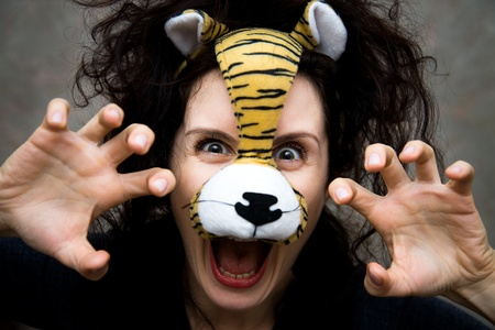 ridiculous: The young woman with curly hair in a mask of a tiger with bright emotions Stock Photo