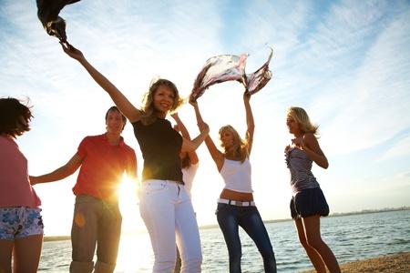 Gruppe von gl�cklichen jungen Menschen tanzen am Strand auf der sch�nen Sommertag