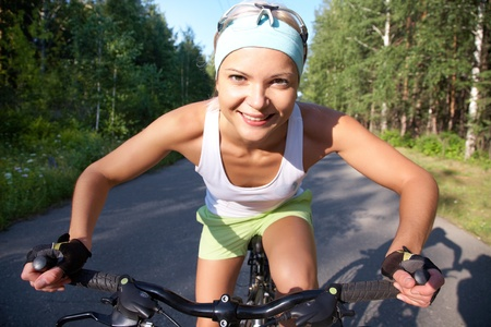 Portrait of a young sports cute girl on a bicycle in the park Stock Photo - 10229311