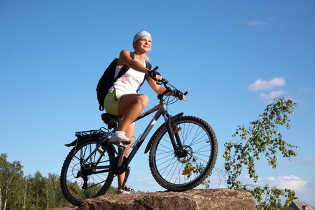 Young beautiful girl on a mountain bike and the blue sky in the park photo