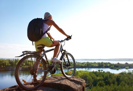 andando en bicicleta: Chica en moto est� alta de una colina y espera que los espacios abiertos naturales