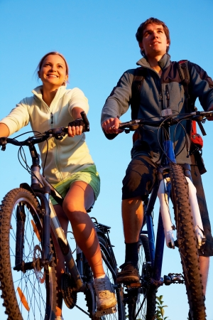 young couple of bicycles look  on sunset outdoor photo