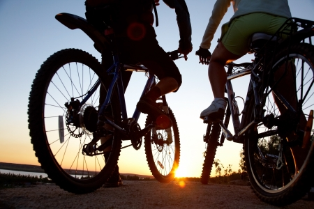 Couple of bicyclists on the brink of  rock looks at sunset photo