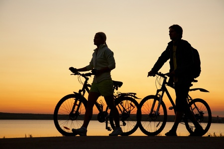 Image of sporty couple with bicycles walking  outdoors against sunset. Silhouette. photo