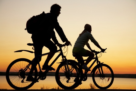 Image of sporty couple on bicycles outdoors against sunset. Silhouette. photo