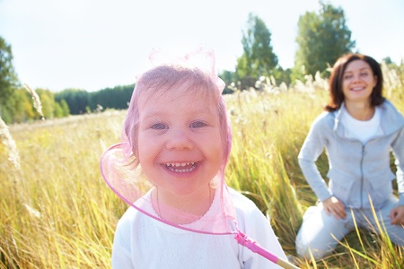 Young beautiful woman playing with her little cute girl in the meadow photo