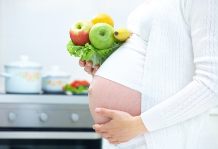 unrecognizable pregnant woman with healthy food in kitchen Stock Photo - 10229374