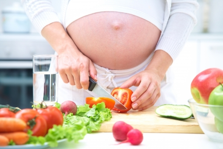 Pregnant woman in kitchen making salad  photo