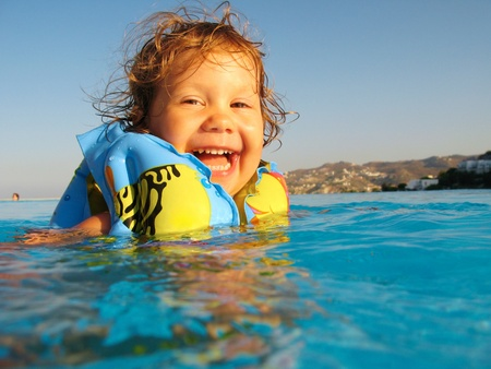 Funny little girl swims in a pool in yellow inflatable armbands photo