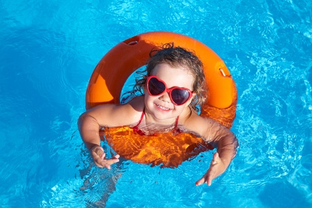 life preserver: Funny little girl swims in a pool in an orange life preserver