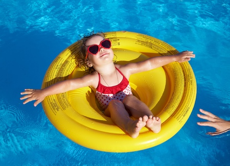Funny little girl swims in a pool in an yellow life preserver photo