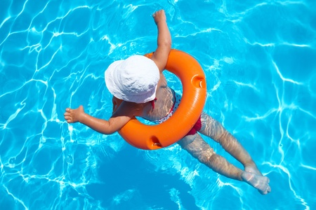 recreational sport: Funny little girl swims in a pool in an orange life preserver