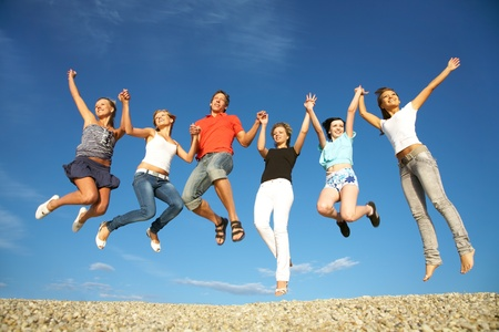 happy people jumping: group of happy young people dancing at the beach on  beautiful summer day