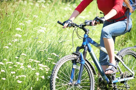 Young cyclist on a mountain bike and the blue sky in the park photo