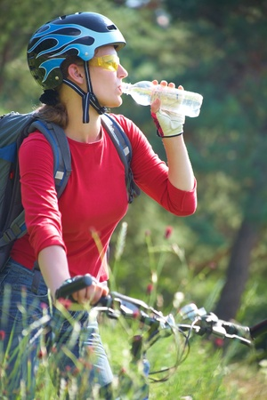 bicyclists: Young cyclist on a mountain bike drinks water