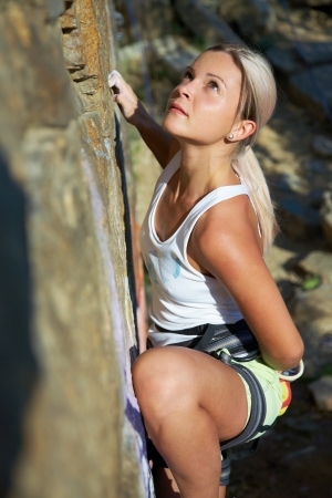 climber: Blonde girl climbing on the rock on background