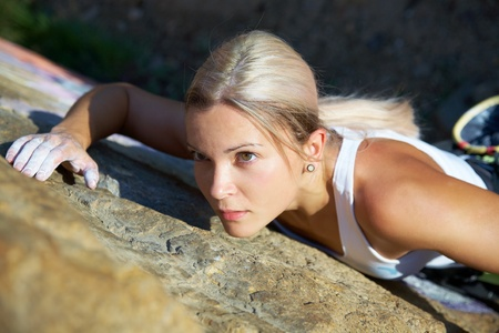 Blonde girl climbing on the rock on background Stock Photo - 10430538
