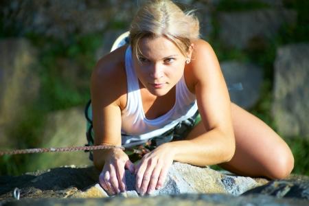 escalando: Chica rubia de escalada en la roca en el fondo