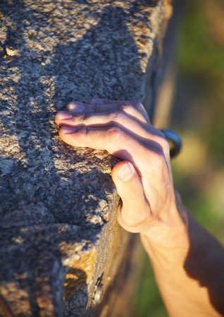 hang body: Rock climbers hand on handhold Stock Photo