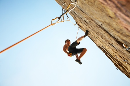 hang body: silhouette of rock climber climbing an overhanging cliff against the blue sky