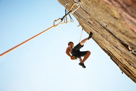 mászó: sziluettje rock törtető mászó egy kiálló szikla a kék ég Stock fotó