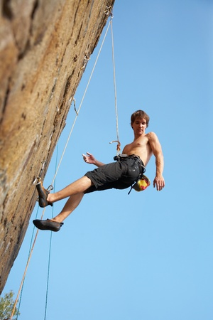 overhanging: rock climber climbing an overhanging cliff against the blue sky  Stock Photo