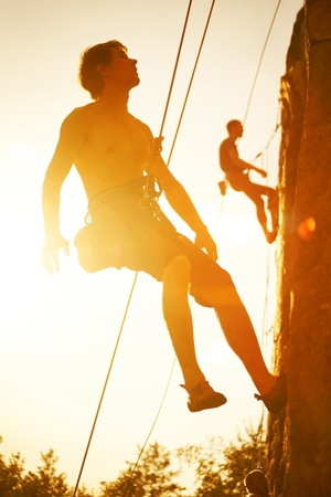 Silhouettes of two men climbing on a cliff at sunset photo