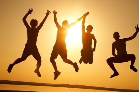 skupina šťastných mladých lidí tančí na pláži na krásnou letní západ slunce