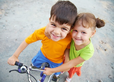 Portrait of cheerful girl and  fun boy with bike on the grey asphalt photo