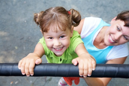 keeping: Portrait of a funny little girl hangs by horizontal bar with mother