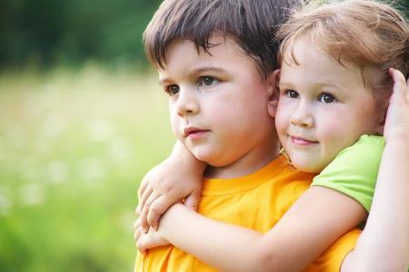 Porträt eines fröhlichen Mädchen und Jungen umarmt Spaß im Freien Standard-Bild