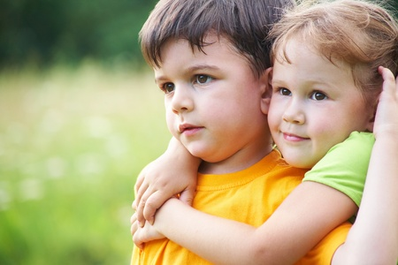 siblings: Portrait of a cheerful girl and boy hugging fun in outdoor