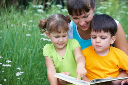 nanny: Young woman reading book little girl and cute boy in a meadow