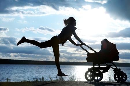 poussette: Silhouette de la m�re mince jeune faisant l'exercice avec un landau