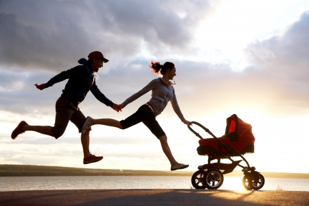 Silhouettes of happy parents are running for a pram photo