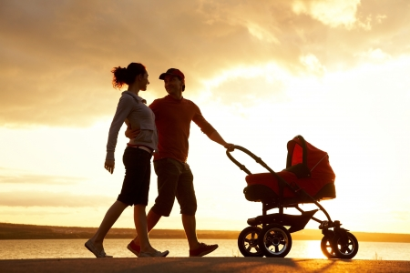 mom and dad: Silhouettes of happy parents walking with stroller on the seacoast