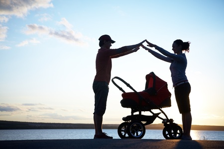 protect family: Silhouettes of parents protect their child in a stroller Stock Photo