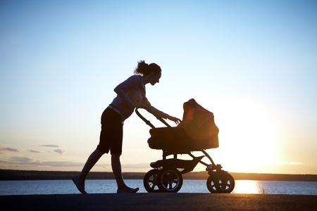 poussette: Silhouette de jeune m�re en appr�ciant la maternit�